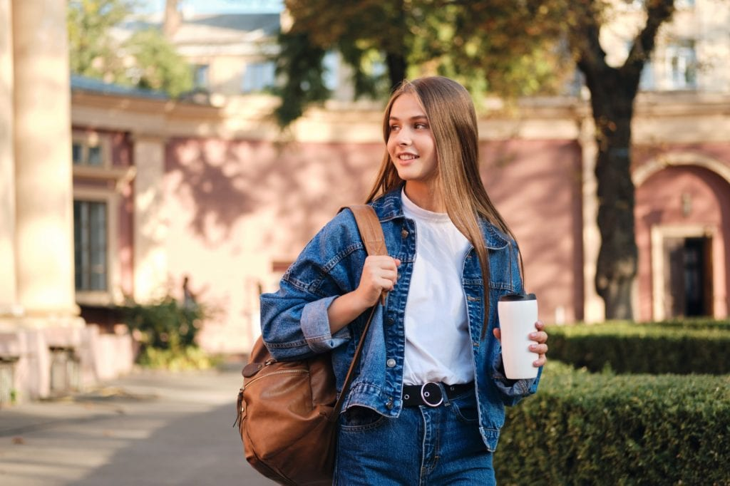Pretty smiling student girl in denim jacket with backpack and coffee on study break for GRE tutoring at American Admissions